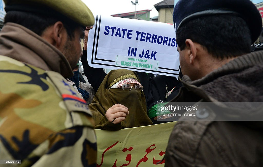 Indian police stops activists of the Jammu and Kashmir Mass Movement (JKMM) during a protest in support of clemency for Mohammad Afzal Guru in Srinagar on December 13, 2012. Indian police detained some half a dozen activists during the protest. Fellow Kashmiri, Mohammad Afzal Guru was sentenced to death by an Indian court after being found guilty of being involved in the 13 September 2001 attack on India's Parliament House in New Delhi. The protestors appealed to the President to commute the death sentence of Guru and reinvestigate the case. AFP PHOTO/Tauseef MUSTAFA