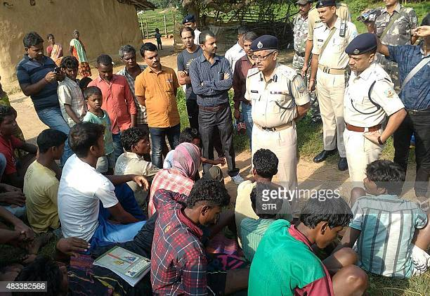 Indian police talk to villagers after five women were killed as they accused of practicing witchcraft in Kanjia village in eastern Jharkhand state on...