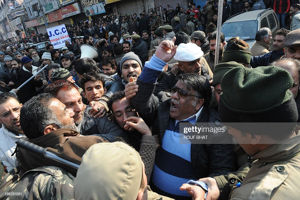 Indian police tussle with Kashmiri state government employees during a protest march in Srinagar on January 10, 2013. Dozens of government employees were arrested as they tried to stage a protest march in Srinagar. Local government employees began a three-day strike January 8 to build pressure on the region's government to take decision on their pending demands which include improvements on contractors wages and retirement benefits. AFP PHOTO/Rouf BHAT