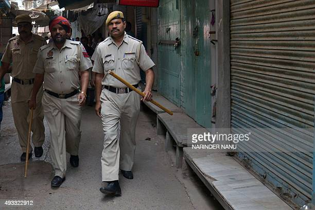 Indian police walk through a market area where Sikh demonstrators had forced a shutdown of shops in Amritsar on October 19 2015 Activists have...