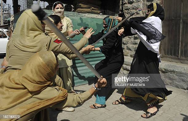 Indian police women beat female Kashmiri nursing students with batons during their arrest at a protest against their exam results in Srinagar on...