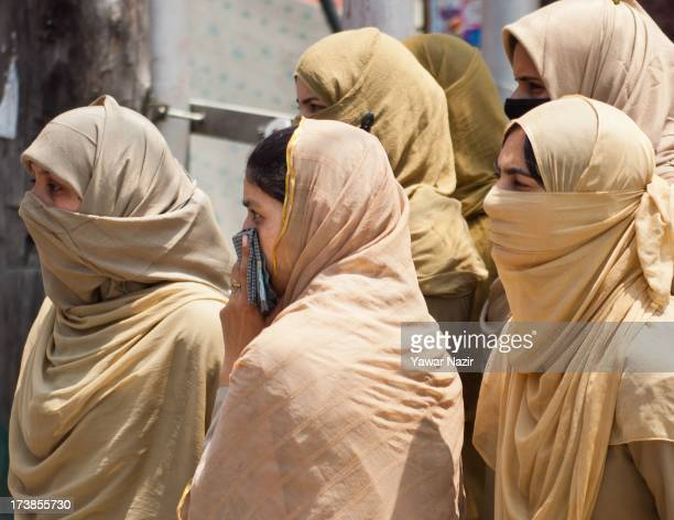 Indian police women look toward the family members of Kashmiri youth who have been sentenced by an Indian court for their alleged involvement in...