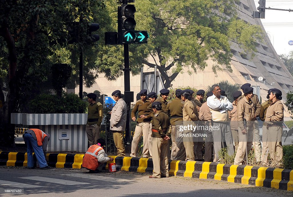 Indian police women stand in the sun light as workers paint the curb on a cold winter morning in New Delhi on January 19, 2013. The northern and central parts of India are under cold spell and fog snarled traffic with passenger trains and flight out of the Indian capital delayed more than seven hours.