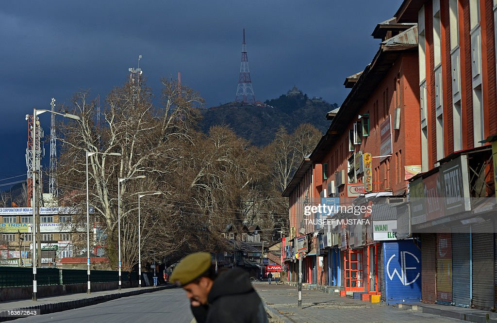 Indian policeman speak on a mobile phone during a curfew, imposed on the Kashmiri summer capital in Srinagar on March 14, 2013. Indian-administered Kashmir's main city was under curfew after the killing of five paramilitary police and the death of two civilians cranked up tensions in the disputed region. AFP PHOTO/ Tauseef MUSTAFA