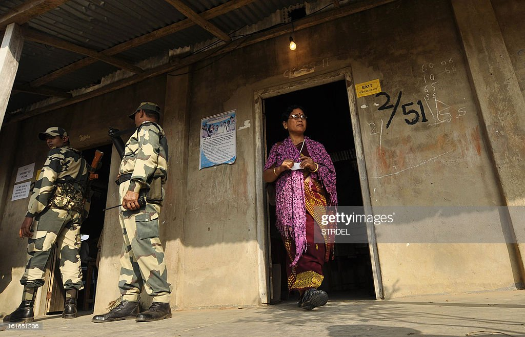 Indian policeman stand guard at a polling station as a voter walks out of a room after casting her ballot at Gamchacobra on the outskirts of Agartala in the northeastern state of Tripura on February 14, 2013. Election to the 60-member state assembly in Tripura, in which the Left Front party is hoping to return to power for a record fifth time, began early today on a peaceful note amidst tight security, official sources said.