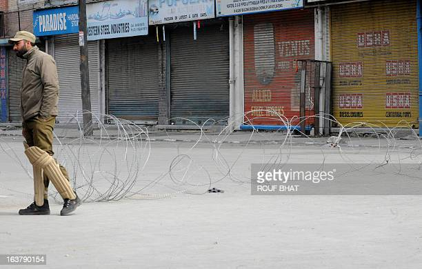 Indian policeman stand guard during the third day of a curfew imposed on the Kashmiri summer capital in Srinagar on March 16 2013 Restrictions have...