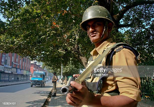 Indian policeman stand guard next to the shuttered shops during a strike on September 27 2012 in Srinagar Kashmir India All businesses schools and...