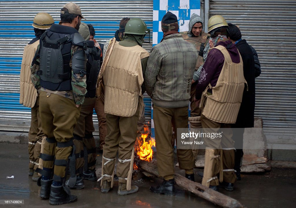 Indian policeman warm themselves on a bonfire as they guard the the streets during a strict curfew on the seventh consecutive day, imposed after the execution of alleged Indian parliament attacker Mohammad Afzal Guru on February 15, 2013 in Srinagar, the summer capital of Indian Administered Kashmir, India. Afzal Guru, from Sopore town in the north of Kashmir, was hung on February 09 for his role in the 2001 Indian parliament attack which left 14 dead. The hanging has further strained relations between India - who blamed the attack on 'Pakistan backed' militant group Jaish-e-Mohammed - and neighbouring Pakistan and has seen an military increase from both along the border.Curfew was lifted from some parts of Srinagar after four days.