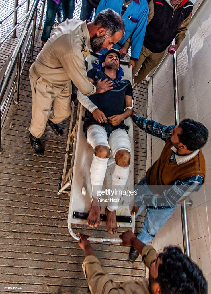 Indian policemen and paramedics carry a wounded Indian policeman on to a gurney inside a hospital after a grenade attack by suspected militants on...