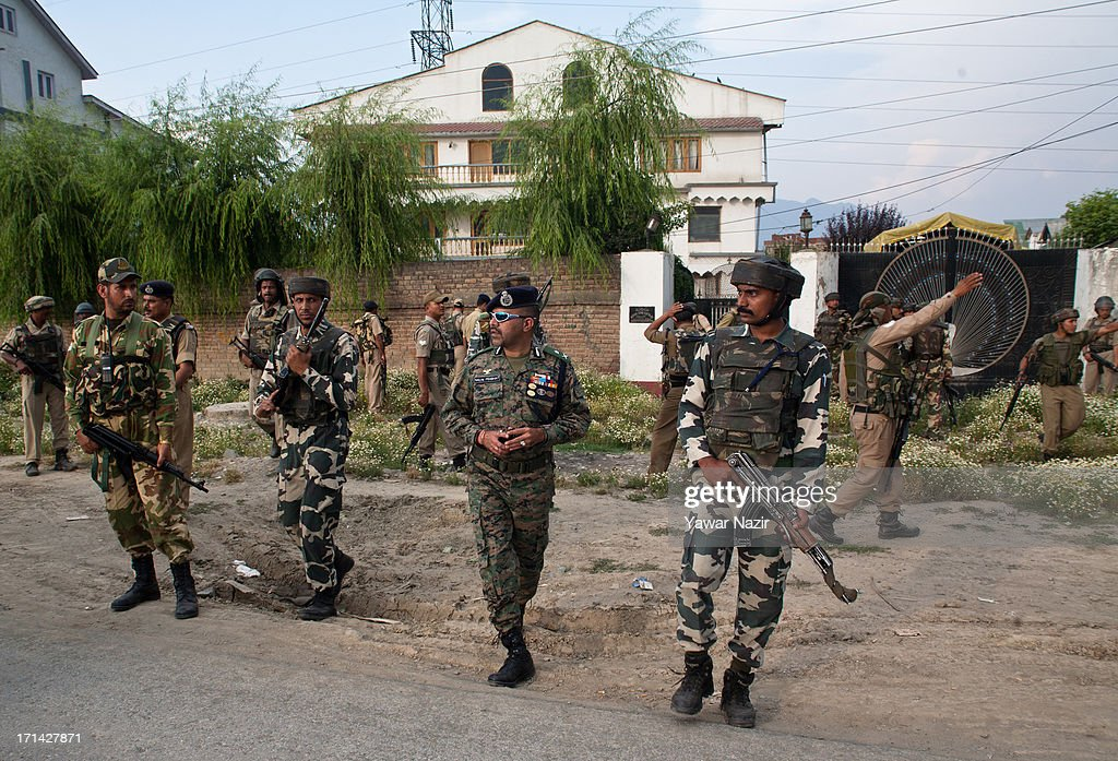 Indian policemen and paramilitary forces search for militants in residential houses after a militant attack on Indian army convoy on June 24, 2013 in Srinagar, the summer capital of Indian administered Kashmir, India. Suspected militants opened fire on an Indian army convoy on the outskirts of Srinagar, killing at least five and wounding seven others, ahead of Indian Prime Minister Manmohan Singh's visit to the disputed Himalayan region tomorrow. The militants fled from the scene and half an hour later hurled a grenade on Indian paramilitary forces in Barzulla area , some two kilometers away. Hizbul-Mujahideen, the largest guerrilla group fighting Indian rule since 1989, claimed responsibility for today's attack, and had just two days before gunned down two policemen in the heart of Srinagar city.