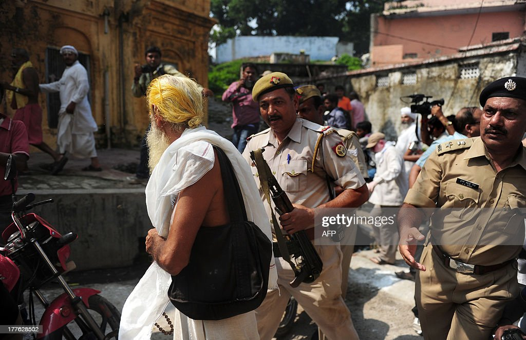 Indian policemen approach a sadhu - holy man - during an attempt by the Vishva Hindu Parishad (VHP) to take out an 84-Kosi Parikrama - procession - in Ayodhya on August 25, 2013. Indian police arrested leaders of a Hindu forum to try and prevent a march to a pilgrimage town where the 1992 razing of a mosque sparked deadly sectarian riots. Organisers from the Vishwa Hindu Parishad (VHP, World Hindu Council) and the Press Trust of India (PTI) said some 125 people were detained in the northern state of Uttar Pdaesh. AFP PHOTO/ SANJAY KANOJIA