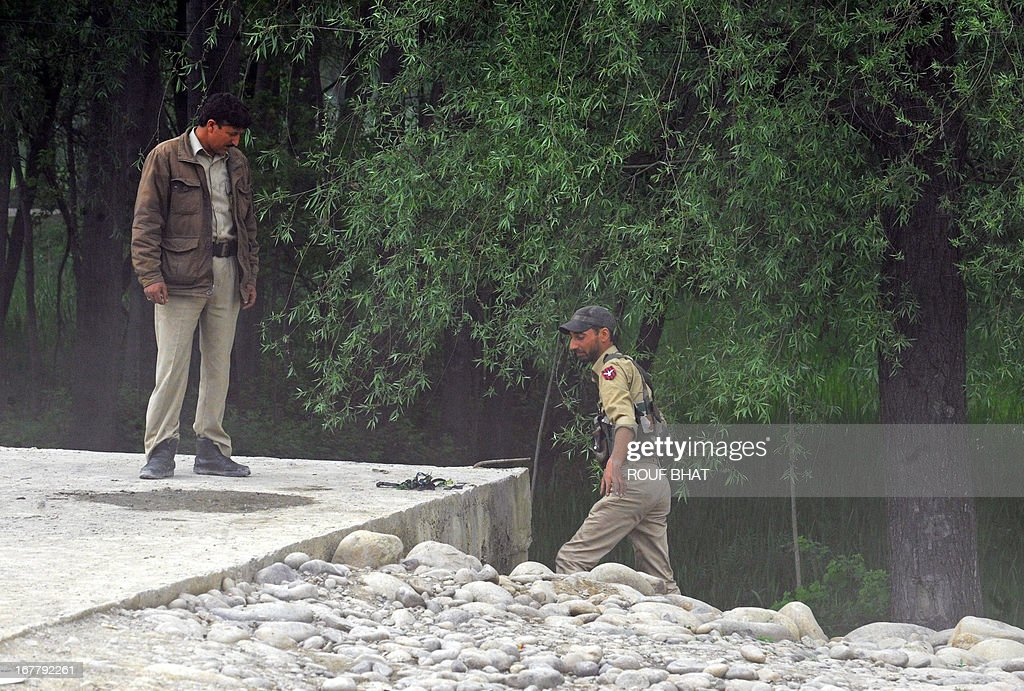 Indian policemen are pictured at the scene where an explosive device was found under a culvert on a main road in the outskirts of Srinagar on April 30, 2013. The road leads to frontier areas of disputed Kashmir and is frequently used by the Indian army. The device was later defused by a police bomb disposal squad.