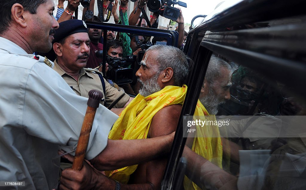 Indian policemen arrest a sadhu - holy man - during an attempt by the Vishva Hindu Parishad (VHP) to take out an 84-Kosi Parikrama - procession - in Ayodhya on August 25, 2013. Indian police arrested leaders of a Hindu forum to try and prevent a march to a pilgrimage town where the 1992 razing of a mosque sparked deadly sectarian riots. Organisers from the Vishwa Hindu Parishad (VHP, World Hindu Council) and the Press Trust of India (PTI) said some 125 people were detained in the northern state of Uttar Pdaesh. AFP PHOTO/ SANJAY KANOJIA