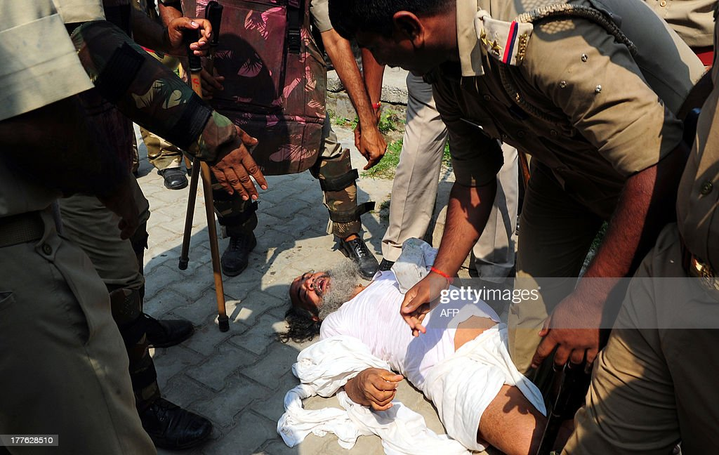 Indian policemen arrest a sadhu - holy man - during an attempt by the Vishva Hindu Parishad (VHP) to take out an 84-Kosi Parikrama - procession - in Ayodhya on August 25, 2013. Indian police arrested leaders of a Hindu forum to try and prevent a march to a pilgrimage town where the 1992 razing of a mosque sparked deadly sectarian riots. Organisers from the Vishwa Hindu Parishad (VHP, World Hindu Council) and the Press Trust of India (PTI) said some 125 people were detained in the northern state of Uttar Pdaesh.