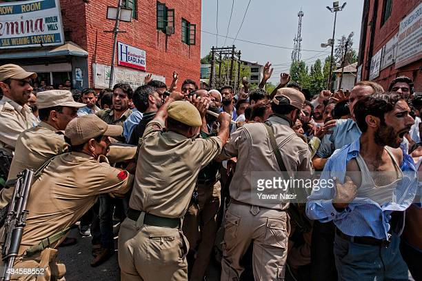 Indian policemen block protesting Kashmiri government Public Health Engineering employees as they shout anti government slogans during a protest...