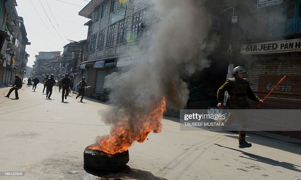 Indian policemen chase a group of Kashmiri protestors during a spontaneous strike to protest the death of 28 year old Kashmiri student, Mudassir Qamran Malla in the Indian city of Hyderabad at the weekend, in Srinagar on March 5, 2013. The Kashmiri student was buried in his native village in the Pulwama district on Monday with the family rejecting the police claim that he had commited suicide. AFP PHOTO/Tauseef MUSTAFA