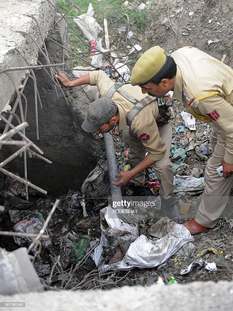 Indian policemen collect evidence from the scene where an explosive device was found under a culvert on a main road in the outskirts of Srinagar on April 30, 2013. The road leads to frontier areas of disputed Kashmir and is frequently used by the Indian army. The device was later defused by a police bomb disposal squad. AFP PHOTO/ROUF BHAT
