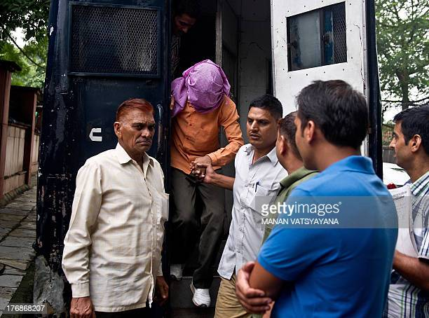 Indian policemen escort the juvenile accused in the December 2012 gangrape of a student from a police vehicle outside the juvenile court in New Delhi...