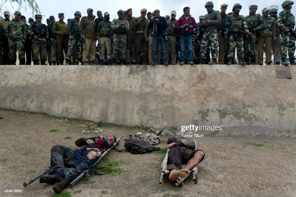 Indian policemen gather around the dead bodies of militants killed in a brief gun battle between Indian government forces and them on April 13, 2014, in Khrew 35 Km south of Srinagar, the summer capital of Indian administered Kashmir, India.Two Indian policemen and two militants were killed after militants allegedly attacked a house of a ruling National Conference (NC) activist in south Kashmir's Pulwom district. After being stopped at the main gate of NC activist Yawar Masudi, militants fired indiscriminately at Indian police guards. Both the militants who had taken cover close to NC leader's house in Gotran were then killed in a firefight with police. The attack was the first in Kashmir during Indian elections being held over five weeks, though it was in an area scheduled to vote in two weeks.