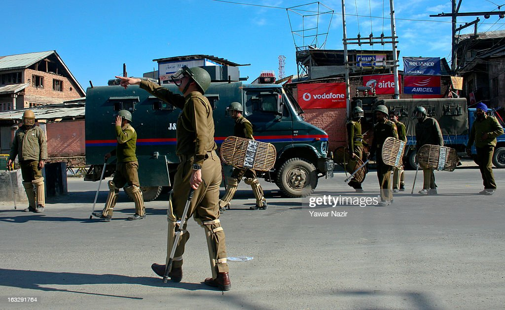 Indian policemen guard a road during a curfew-like restriction on March 7, 2013 in Srinagar, the summer capital of Indian Administered Kashmir, India. Clashes erupted in most parts of Kashmir today leaving scores of people injured. Meanwhile Indian authorities imposed curfew-like restrictions for the second consecutive day in most parts of Kashmir following the killing of a Kashmiri youth by the Indian army in North Kashmir's Baramulla district.
