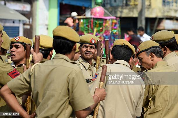 Indian policemen keep watch during an Ashura procession at Trilokpuri in eastern New Delhi on November 4 2014 Ashura mourns the death of Imam Hussein...