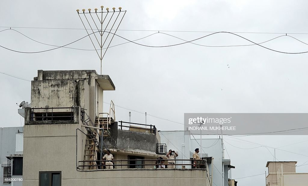Indian policemen keep watch from atop the refurbished Nariman (Chabad) House after its formal reopening in Mumbai on August 26, 2014. A Jewish centre in Mumbai reopened, nearly six years after heavily armed militants stormed the building and killed six people inside during the 2008 attacks on the city. One of several high-profile targets assaulted by the gunmen, Chabad House in south Mumbai was left bullet-ridden and bereft of its directors Rabbi Gavriel Holtzberg and his pregnant wife Rivky, who were both slain in the siege. They were among 166 people killed in the three-day onslaught in November 2008, which also targeted luxury hotels, a popular cafe and a train station.
