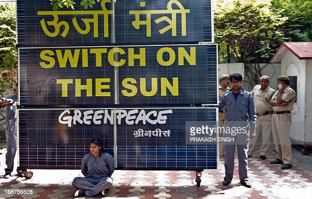Indian policemen look on as Greenpeace activists chained to a bank of solar panels block the entry to the residence of Delhi's Power Minister Haroon...