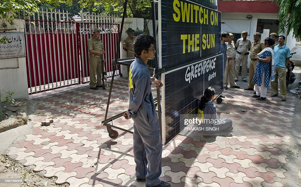 Indian policemen look on as Greenpeace activists chained to a bank of solar panels block the entry to the residence of Delhi's Power Minister Haroon Yusuf in New Delhi on May 15, 2013. Greenpeace activists demanded that Delhi Government should take steps to improve its performance on the use of renewable source of energy to deal with capital's power crisis. AFP PHOTO/Prakash SINGH