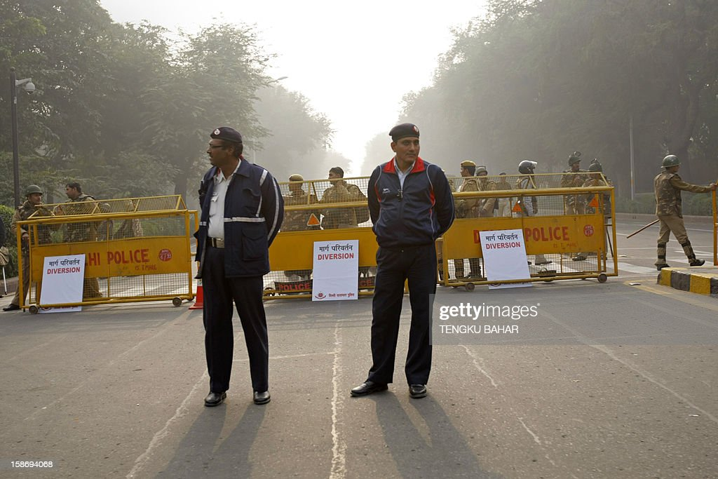 Indian policemen look on as they keep watch along a sealed-off road leading towards the landmark India Gate monument following weekend clashes between demonstrators and police in New Delhi on December 24, 2012. Indian Prime Minister Manmohan Singh has appealed for calm and vowed to protect women as police struggled to quell increasing outrage over sex crimes following the gang-rape of a student.