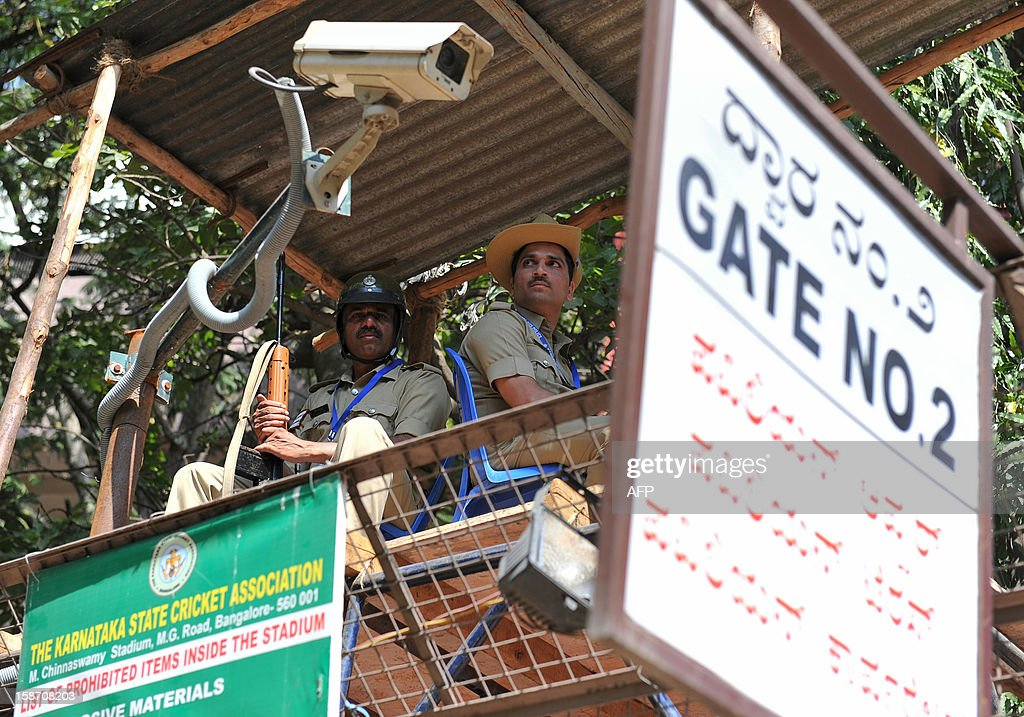 Indian policemen look on from a tower at an entrance to The M. Chinnaswamy Stadium in Bangalore on December 25, 2012. Police were out in full force in the southern Indian city as part of a massive security operation ahead of Pakistan's first cricket tour of India for five years. AFP PHOTO/Manjunath KIRAN