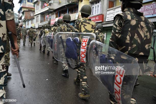 Indian policemen patrol along a street during clashes with Gorkhaland supporters during an indefinite strike called Gorkha Janamukti Morcha in...