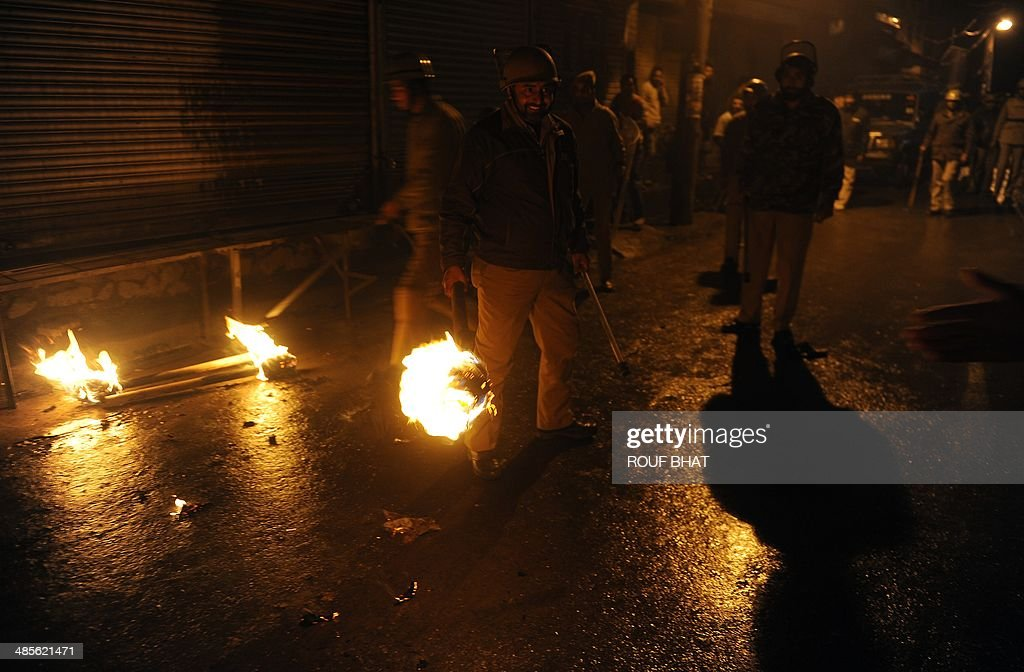 Indian policemen pick up torches thrown at them by Jammu Kashmir Liberation Front (JKLF) activists in Srinagar on April 19, 2014 during a rally against the ongoing Indian general elections. JKLF and several other separatist organisations have jointly appealed to the people of Jammu and Kashmir to boycott Indian parliamentary elections. India's 814-million-strong electorate is voting in the world's biggest election which is set to sweep the Hindu nationalist opposition to power at a time of low growth, anger about corruption and warnings about religious unrest. AFP PHOTO/Rouf BHAT