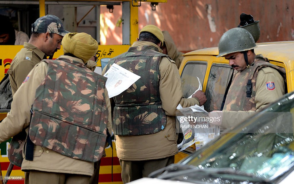 Indian policemen read newspapers as they stand alert on a street in New Delhi on December 29, 2012, as Indian leaders appealled for calm fearing fresh outbursts of protests after the death of a gang-rape victim. New Delhi's top police officer and chief minister have urged people to mourn the death of a gang-rape victim in a peaceful manner as large parts of the city-centre were sealed off. The calls for calm came after an Indian woman who was gang-raped on a New Delhi bus died in a Singapore hospital after suffering severe organ failure. AFP PHOTO/RAVEENDRAN