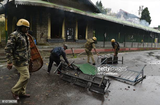Indian policemen remove a barricade near the train station set alight during clashes with Gorkhaland supporters during an indefinite strike called...