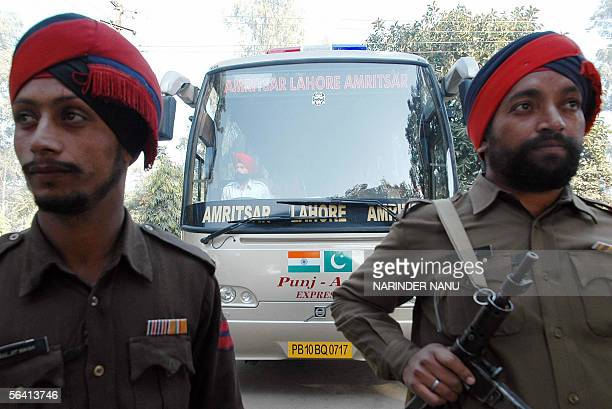Indian policemen stand beside a bus carrying local officials on its way to cross the IndiaPakistan border at Wagah in India's northern state of...
