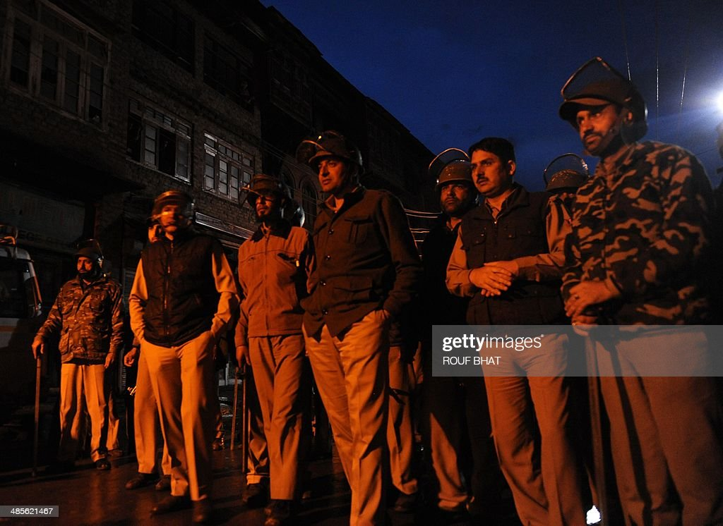 Indian policemen stand guard as Jammu Kashmir Liberation Front (JKLF) activists hold a rally against the ongoing Indian general elections in Srinagar on April 19, 2014. JKLF and several other separatist organisations have jointly appealed to the people of Jammu and Kashmir to boycott Indian parliamentary elections. India's 814-million-strong electorate is voting in the world's biggest election which is set to sweep the Hindu nationalist opposition to power at a time of low growth, anger about corruption and warnings about religious unrest. AFP PHOTO/Rouf BHAT