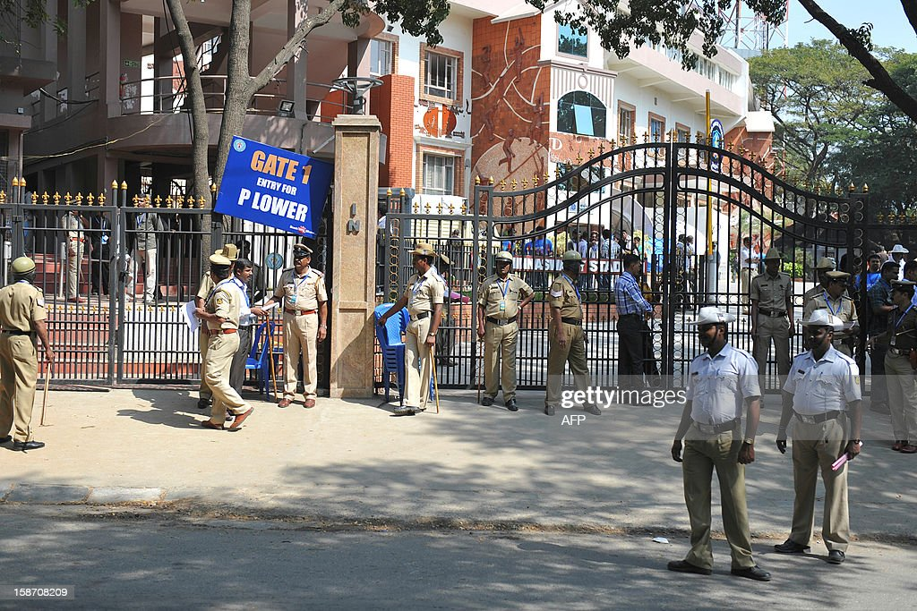 Indian policemen stand guard at the main gate of The M. Chinnaswamy Stadium in Bangalore on December 25, 2012. Police were out in full force in the southern Indian city as part of a massive security operation ahead of Pakistan's first cricket tour of India for five years. AFP PHOTO/Manjunath KIRAN