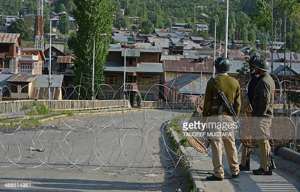 Indian policemen stand guard behind a barbed wire fence in restive Kashmir's Baramulla constituency on May 7 where elections are being held with the...