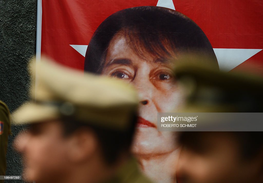 Indian policemen stand near a poster bearing a portrait of Myanmar opposition leader and National League for Democracy Chairperson Aung San Suu Kyi near the entrance of a school in New Delhi on November 16, 2012. The Nobel laureate, on a visit to neighbouring India and who is now a member of parliament after dramatic changes overseen by a quasi-civilian regime that took power last year, was released from military house arrest in 2010. AFP PHOTO/Roberto Schmidt