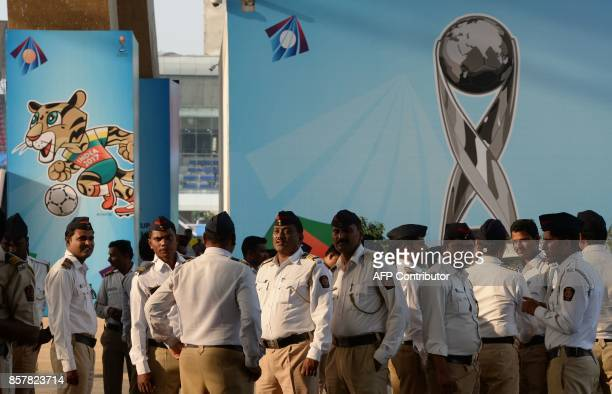 Indian policemen stand near the poster of FIFA U17 football World trophy at The DY Patil stadium in Navi Mumbai on October 5 2017 The FIFA U17...