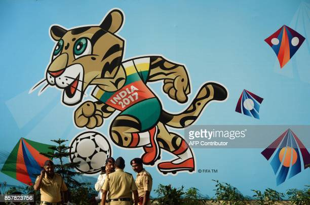 Indian policemen stand near the poster of FIFA U17 football World Cup mascot at The DY Patil stadium in Navi Mumbai on October 5 2017 The FIFA U17...