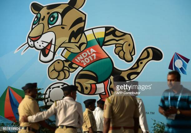 Indian policemen stand near the poster of FIFA U17 football World mascot trophy at The DY Patil stadium in Navi Mumbai on October 5 2017 The FIFA U17...