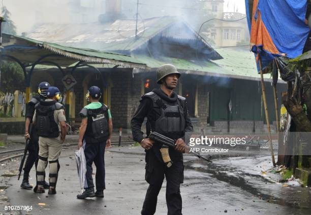 Indian policemen stand near the train station set alight during clashes with Gorkhaland supporters during an indefinite strike called Gorkha...