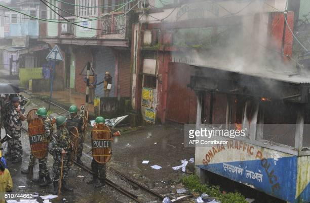 Indian policemen stand next to police station set alight during clashes with Gorkhaland supporters during an indefinite strike called by Gorkha...