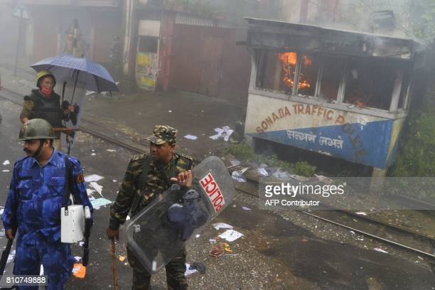 Indian policemen stand next to police station set alight during clashes with Gorkhaland supporters during an indefinite strike called Gorkha...