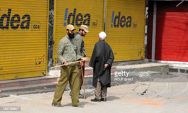 Indian policemen stop a Kashmiri Muslim pedestrian during the third day of curfew imposed on the Kashmiri summer capital in Srinagar on March 16 2013...