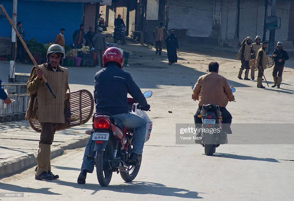 Indian policemen stop a scooter during a curfew-like restriction on March 7, 2013 in Srinagar, the summer capital of Indian Administered Kashmir, India. Clashes erupted in most parts of Kashmir today leaving scores of people injured. Meanwhile Indian authorities imposed curfew-like restrictions for the second consecutive day in most parts of Kashmir following the killing of a Kashmiri youth by the Indian army in North Kashmir's Baramulla district.