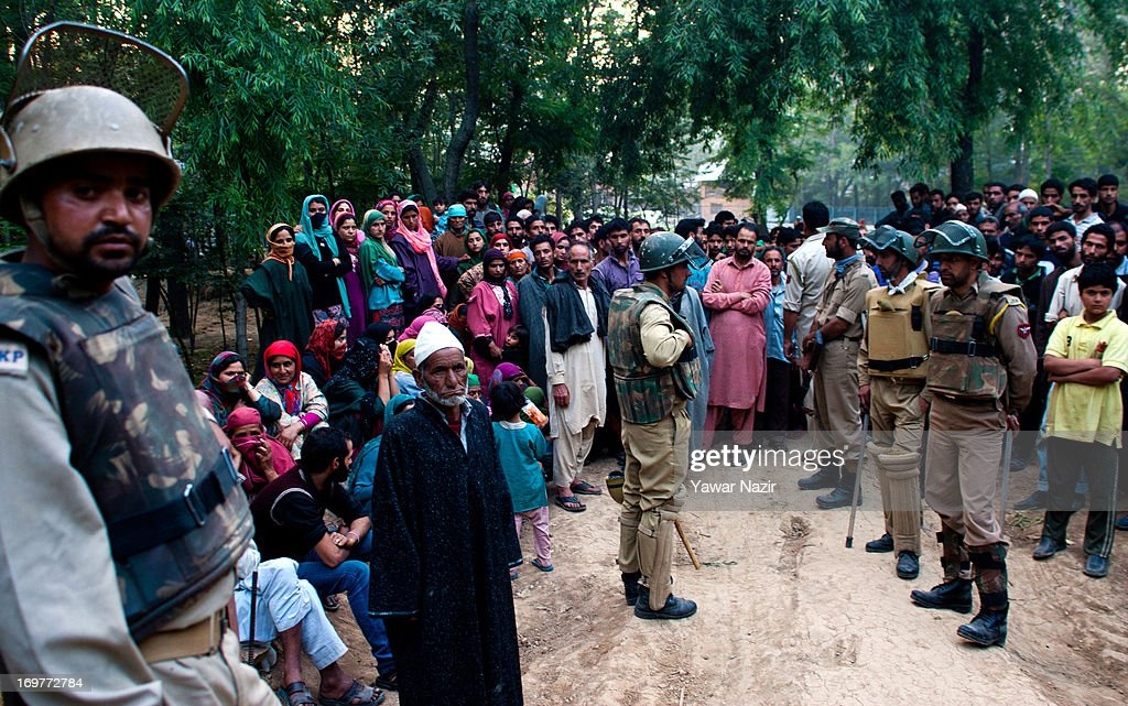Indian policemen stop Kashmiris from reaching their village where a gun battle between militants and Indian military forces was taking place on June 1, 2013 in Wachi, 49 km (30 miles) south of Srinagar, the summer capital of Indian administered Kashmir, India. Two militants belonging to Hizbul Mujahideen, the largest militant outfit operating in Indian Administered Kashmir, were killed in the gun battle that started between militants and Indian military forces in South Kashmir yesterday and ended this evening, police said here. This was the second gun battle between militants and Indian military forces in South Kashmir in the span of one week. Last week, militants killed five Indian army soldiers, while a militant was also killed.