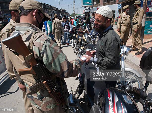 Indian policemen stop motorcyclists for checking ahead of the Lok Sabha elections on April 28 2014 in Srinagar the summer capital of Indian...