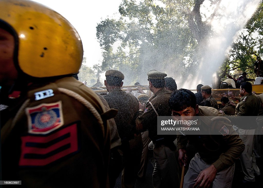Indian policemen take cover from a water-canon during a protest outside the Sri Ram College of Commerce in New Delhi on February 6, 2013. Indian riot police fired water cannon on Wednesday at hundreds of students outside a college in New Delhi who were protesting an appearance by hardline nationalist politician Narendra Modi. Modi, tipped to be the main opposition Bharatiya Janata Party's (BJP) candidate for prime minister in elections next year, was speaking at the Sri Ram College of Commerce.
